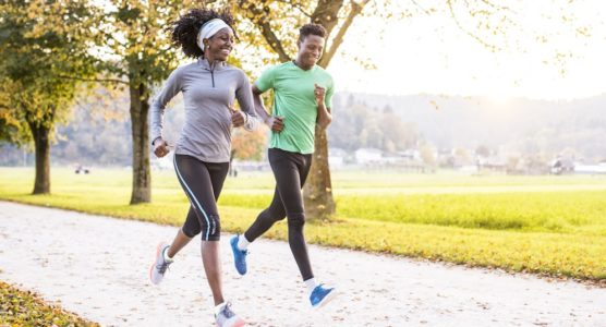 Two-people-running-through-a-park-min